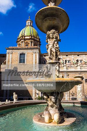 Central statues of the Pretoria Fountain with the Dome of Chiesa di San Giuseppe dei Teatini  church in the background in Piazza Pretoria (Pretoria Square) in the historic center of Palermo in Sicily, Italy