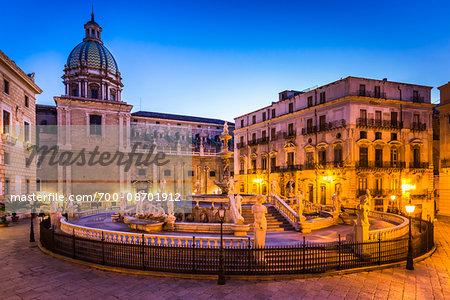 The grand Pretoria Fountain in Piazza Pretoria (Pretoria Square) illuminated at dusk with the Dome of Chiesa di San Giuseppe dei Teatini in the background, historic center of Palermo in Sicily, Italy