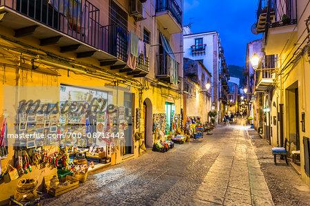 Shops along Narrow Street at Night in Cefalu, Sicily, Italy