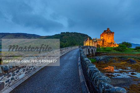 Eilean Donan Castle illuminated at dusk with footbridge near Kyle of Lochalsh in Scotland, United Kingdom