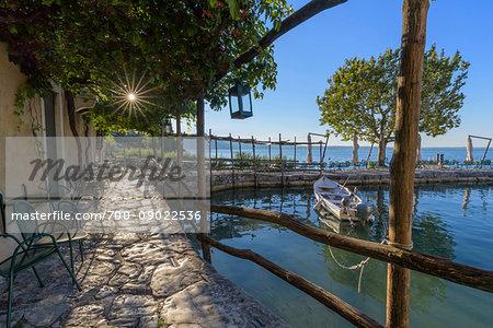 Sun shining on the stone patio at Locanda San Vigilio overlooking a little harbor and Lake Garda in the morning at Punta San Vigilio in Garda, Veneto, Italy