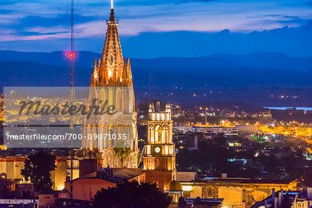 The Parroquia de San Miguel Arcangel and the Iglesia de San Rafael with the city center of San Miguel de Allende at dusk in Guanajuato, Mexico