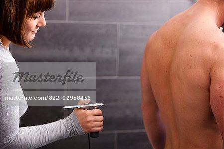 Woman spraying fake tan on man's back with airbrush gun