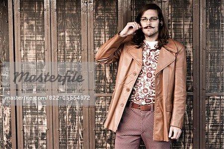 Man Standing in front of Shutters Tweaking Moustache