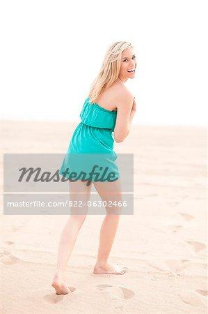 Smiling Woman Walking on Beach