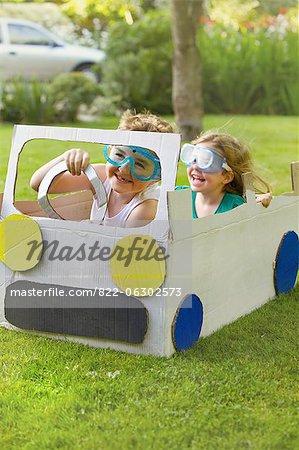 Boy and Girl Wearing Goggles Driving Cardboard Car