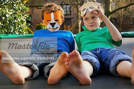 Two Boys Wearing Masks Lying on Trampoline