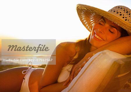 Smiling Woman Wearing Straw Hat Lying on Sun Lounger