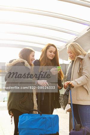 Teenage Girls at Airport Terminal Using Smart Phone
