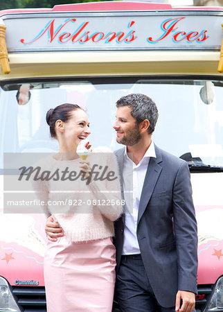 Smiling Couple Standing in front of Ice cream Van