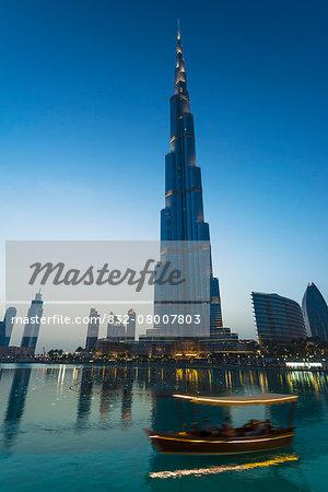 Boat going around artificial lake at sunset in front of the Burj Khalifa; Dubai, United Arab Emirates