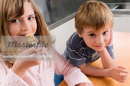 Portrait of a girl having breakfast beside her brother