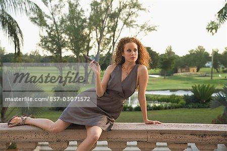Woman sitting on balustrade and smoking a cigar,Biltmore Hotel,Coral Gables,Florida,USA