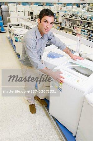 Man buying washing machine in a supermarket