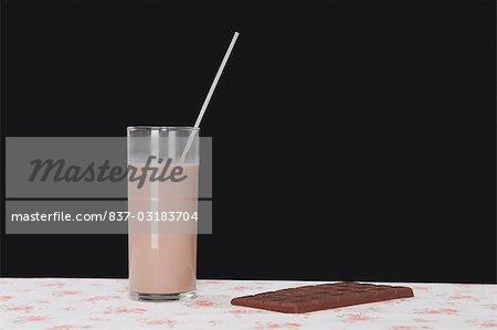 Chocolate milkshake with a chocolate bar on a table