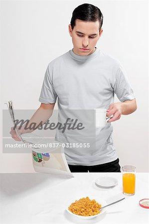 Man reading a newspaper at breakfast