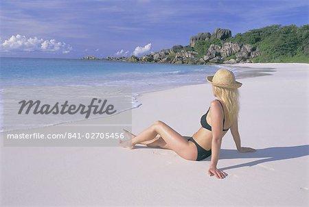 Woman sitting on the beach, Grand Anse, La Digue Island, Seychelles, Indian Ocean, Africa