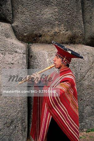 Portrait of a Peruvian man playing a flute, Inca ruins of Sacsayhuaman, Cuzco, Peru, South America