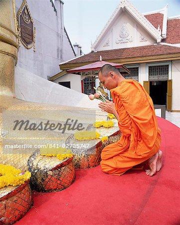 Buddhist monk kneeling and praying at the feet of a standing Buddha, Wat Intharawihan, Bangkok, Thailand, Southeast Asia, Asia