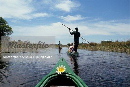 Tourists in dug out canoe (mokoro), Okavango Delta, Botswana, Africa