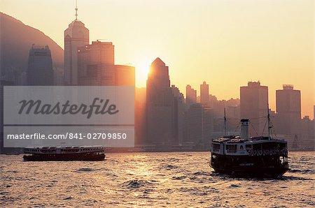 Star ferries, Victoria Harbour and Hong Kong Island skyline at sunset, Hong Kong, China, Asia