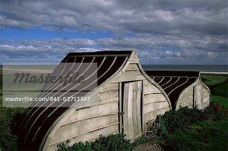 Upturned boats used as sheds, Lindisfarne (Holy Island), Northumbria, England, United Kingdom, Europe