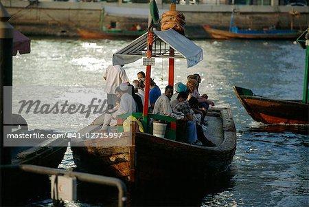 People on a local ferry boat in Dubai Creek, Dubai, UAE