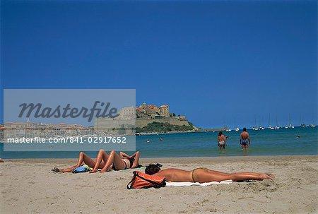 Tourists sunbathing on beach near Calvi, Balagne region, Corsica, France, Europe