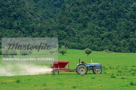 Spraying fertiliser on field for sheep grazing on coastal area near Hokitka, South Island, New Zealand, Pacific