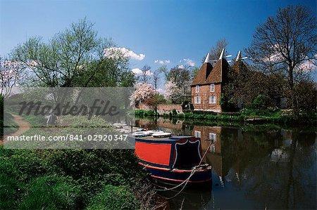 Brightly painted barge and oast houses on the River Medway, Yalding, near Maidstone, Kent, England, United Kingdom, Europe