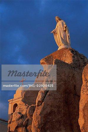 Dawn light on statue of the Virgin and the Chapel of Notre Dame de la Serra, near Calvi, Balagne region, Corsica, France, Europe