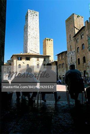 Locals enjoying the shade in the Piazza del Duomo, San Gimignano, Tuscany, Italy, Europe