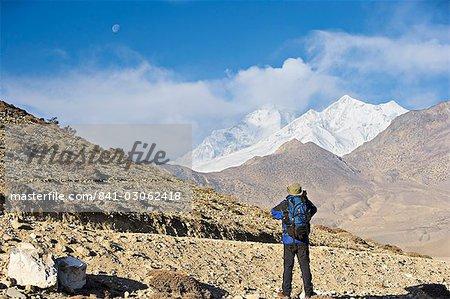 Trekker taking a photo on the Annapurna circuit trek, between Jomsom and Muktinath, Himalayas, Nepal, Asia