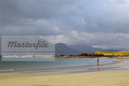 Lone person on a sandy beach under a stormy sky, near Tully Cross, Connemara, County Galway, Connacht, Republic of Ireland, Europe