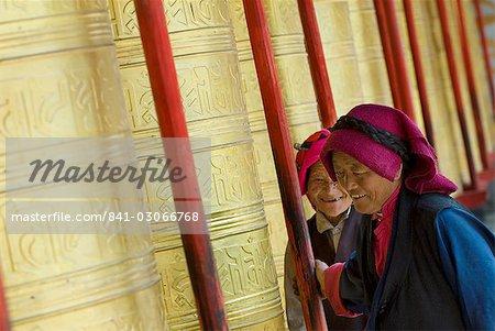 Two old women turning prayer wheels, Tagong temple, Tagong, Sichuan, China, Asia