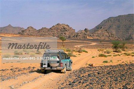 Jeep driving on desert road, Akakus, Sahara desert, Fezzan, Libya, North Africa, Africa