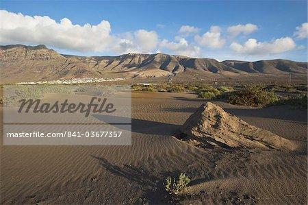 Volcanic cliffs rising to 600m over desert landscape near Famara, with its low-rise bungalow development, Famara, Lanzarote, Canary Islands, Spain, Atlantic Ocean, Europe