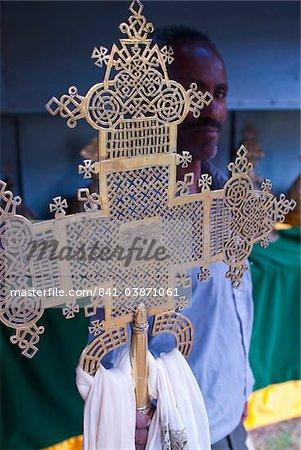 Orthodox monk standing behind a Christian cross, Axum, Ethiopia, Africa