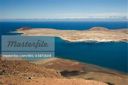 Looking northwest to Caleta del Sebo on Graciosa Island from the Mirador del Rio in the Risco de Famara range in the mountainous north of Lanzarote, Haria, Lanzarote, Canary Islands, Spain, Atlantic, Europe