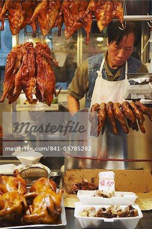 Man selling roast chicken and duck at market, Causeway Bay, Hong Kong, China, Asia