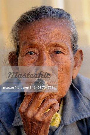 Old woman smokes a marihuana cigar, Bagan, Myanmar, Asia