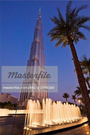 Burj Khalifa and entrance fountains and palm tree at night, Dubai City, United Arab Emirates, Middle East