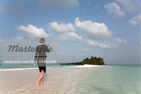 Woman with cell phone on a tropical beach, Kuramathi Island, Ari Atoll, Maldives, Indian Ocean, Asia