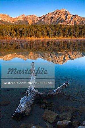 Early morning sunshine glows on Pyramid Mountain, its reflection mirrorlike in Patricia Lake, Jasper National Park, UNESCO World Heritage Site, Alberta, Rocky Mountains, Canada, North America