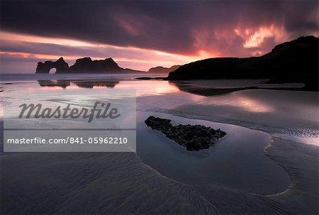 A spectacular sunrise on the beautiful Wharariki Beach, South Island, New Zealand, Pacific