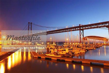 Boats on the River Tagus move at night in the Doca de Santa Amaro marina under the 25 April Bridge, Lisbon, Portugal, Europe