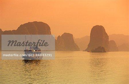 Traditional boat sailing through limestone archipelago at sunset, Ha Long Bay, UNESCO World Heritage Site, Northeast, Vietnam, Indochina, Southeast Asia, Asia