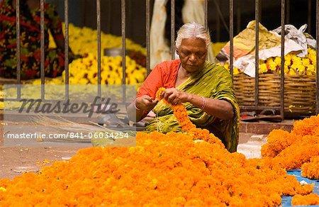 Elderly woman stringing marigold flowers into garlands in the market, Bangalore, Karnataka, India, Asia
