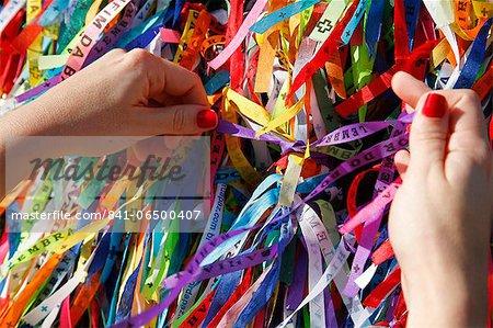 Woman tying lucky ribbon at Igreja Nosso Senhor do Bonfim church, Salvador (Salvador de Bahia), Bahia, Brazil, South America