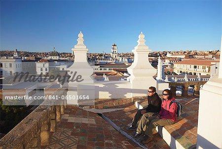 Couple sitting on rooftop of Convento de San Felipe Neri, Sucre, UNESCO World Heritage Site, Bolivia, South America